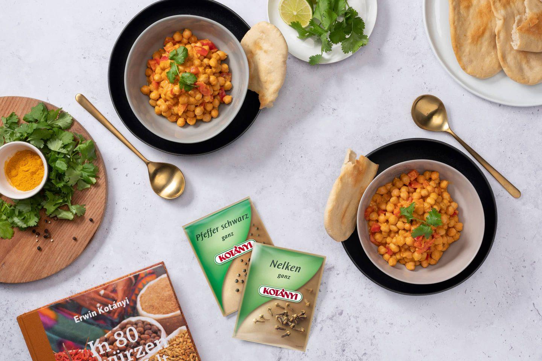 Curry z ciecierzycy z chlebem naan obok torebek z czarnym pieprzem i goździkami.