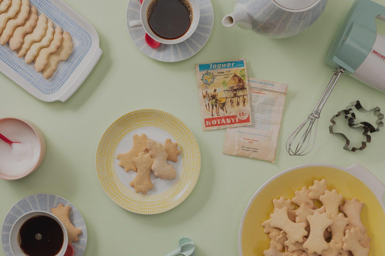 Ciasteczka imbirowe na talerzyku i zestaw do kawy w pastelowych kolorach.