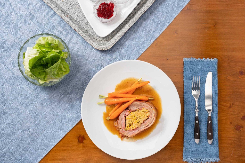 Dwa nadziewane mostki cielęce z glazurowaną marchewką na białym talerzu.