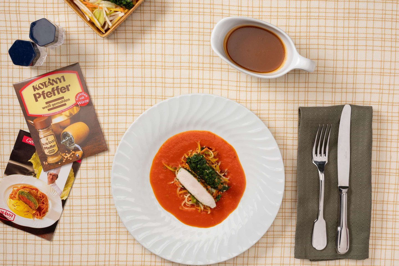 Comber z królika, z sosem paprykowo-śmietanowym z warzywami, obok opakowania białego pieprzu.