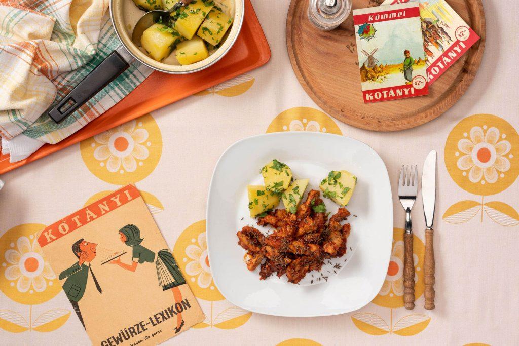 Porcja wieprzowiny z kminkiem, na kwadratowym talerzu z ziemniakami z pietruszką.