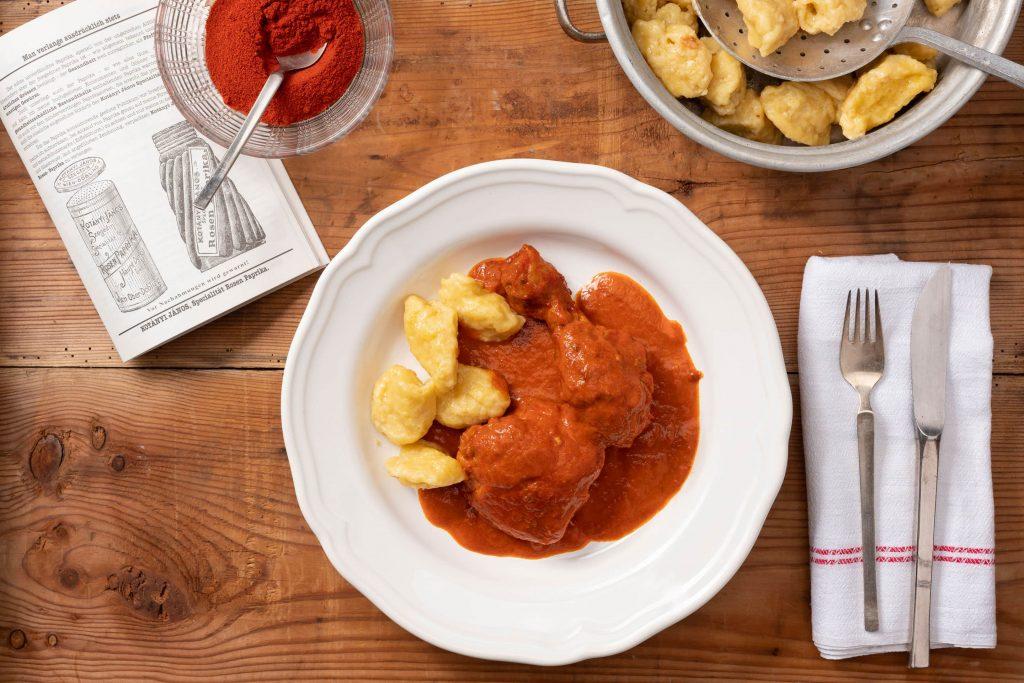 Głęboki talerz z paprykowym kurczakiem i kluskami, w towarzystwie miski wypełnionej mieloną papryką.