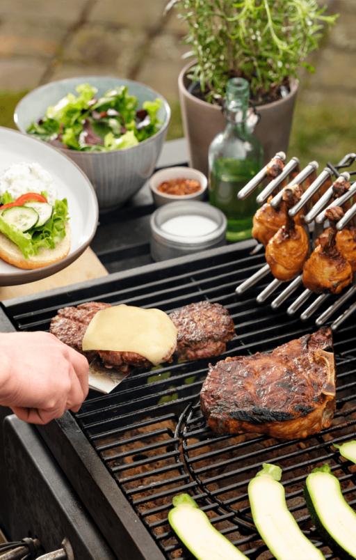 Burgery, udka z kurczaka na stojaku do pokrywek i kotlety na grillu.